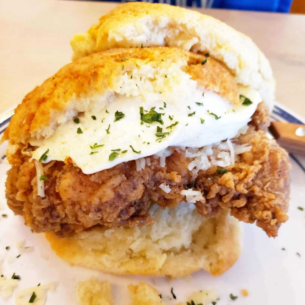 An over easy egg, fried chicken, and Kenny's cheddar cheese sandwiched between two soft, flaky biscuits.